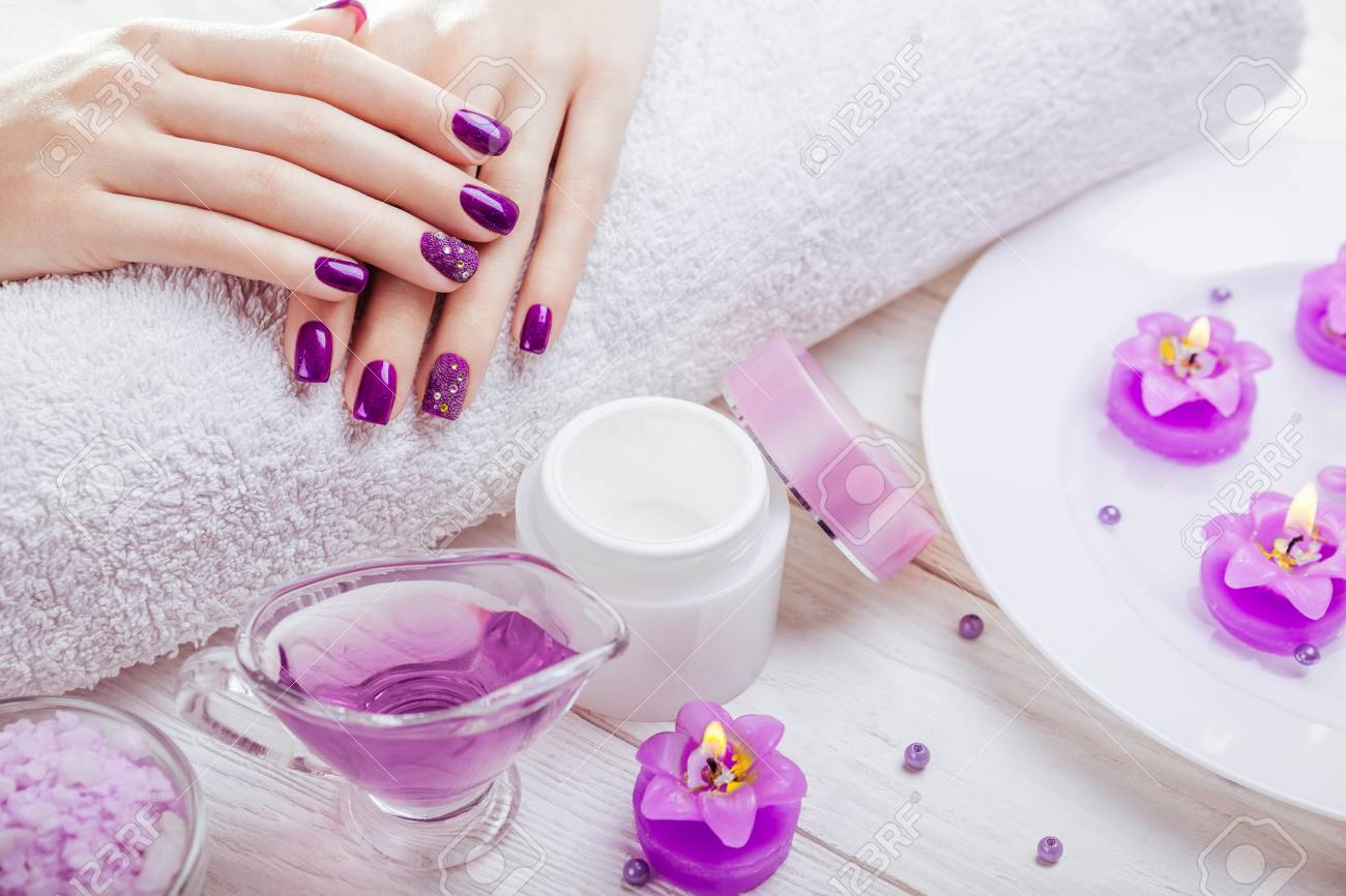 Beautiful purple manicure with spa essentials on wooden background - 95597627