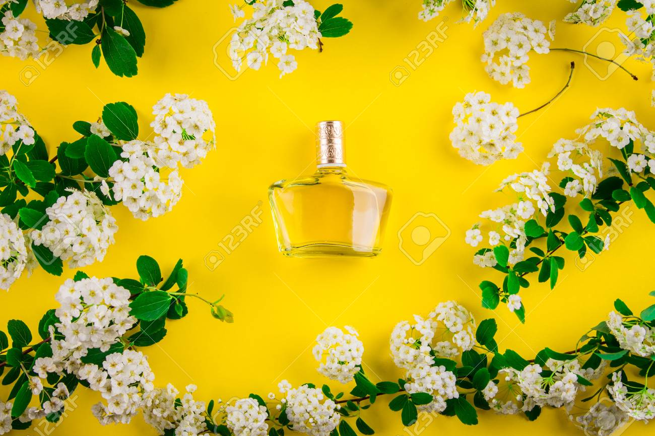 Bottle Of Perfume With White Flowers On Yellow Background Stock