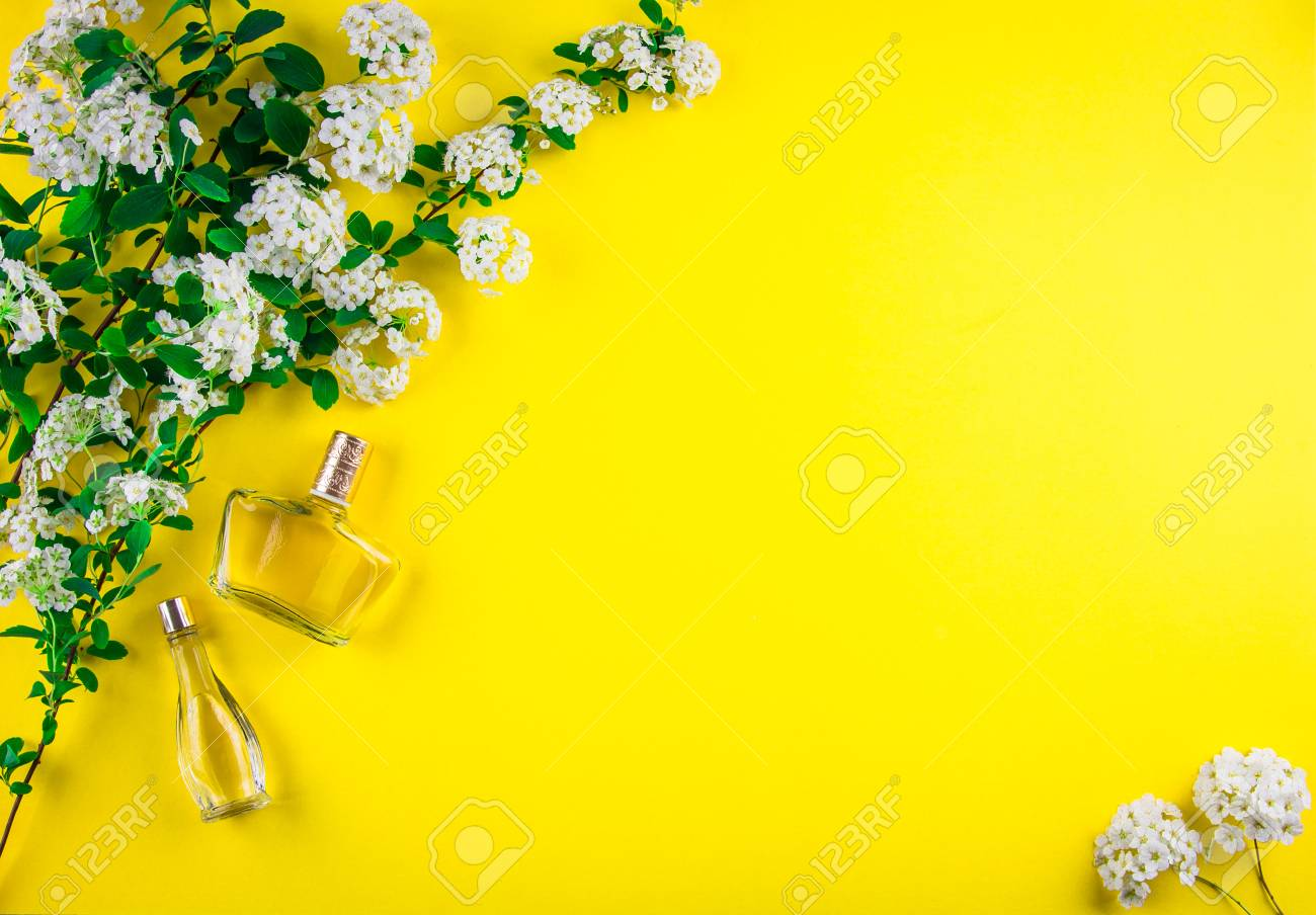Bottles Of Perfume With White Flowers On Yellow Background Stock