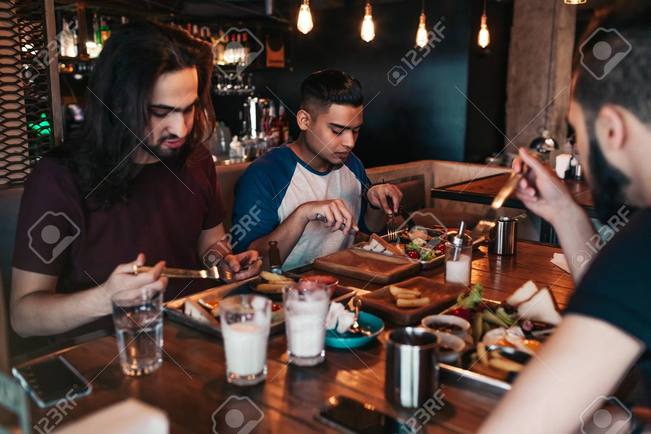 Multiracial friends eating breakfast in cafe  Young arabic men