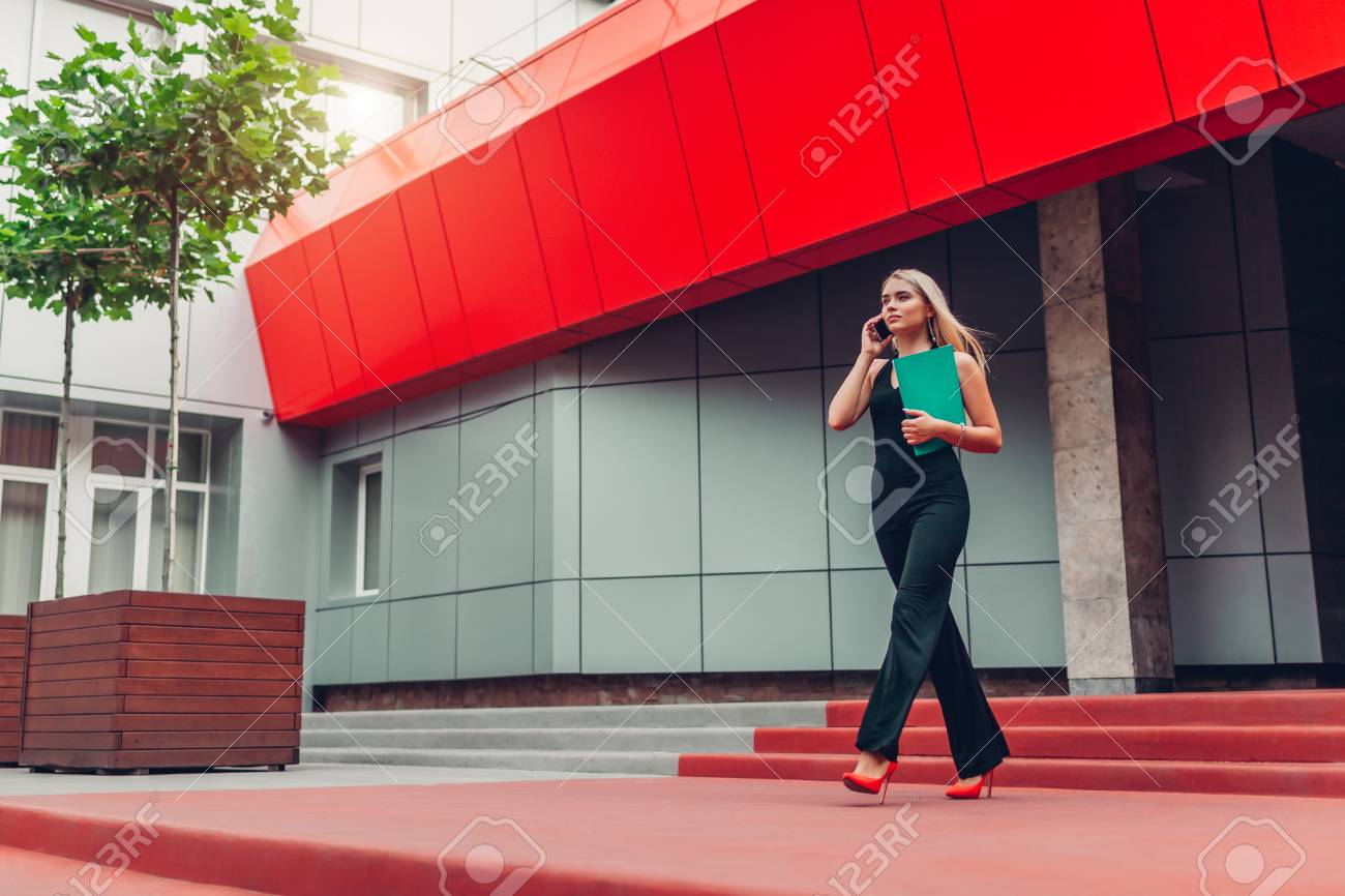 Young blonde businesswoman calling on smartphone and holding folder walking by business center in city. Business, communication, technology and people concept - 105584794