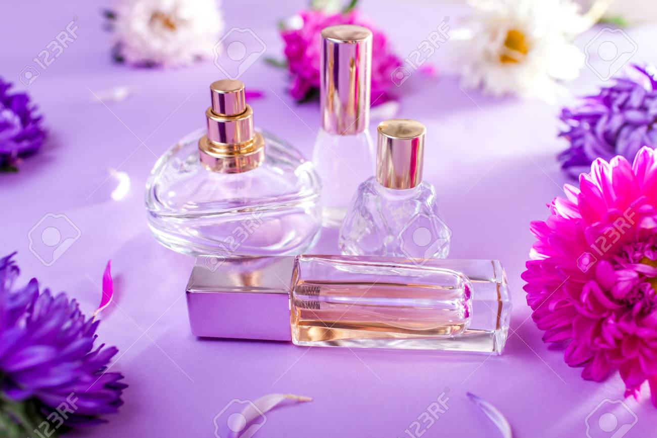 Bottles Of Perfume With Purple And White Flowers On Violet