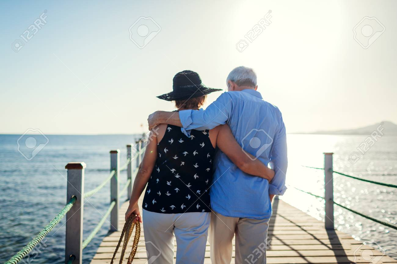Senior couple walking on pier by Red sea. People enjoying vacation. Valentines day - 116784485