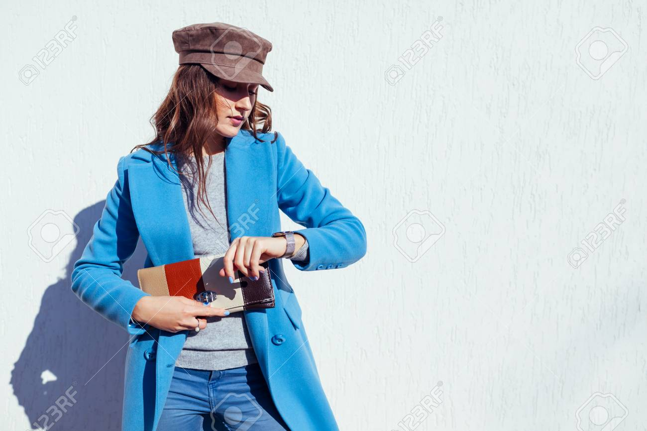 Young woman looking on watch, holding stylish handbag and wearing trendy blue coat and cap. Spring female clothes and accessories. Fashion - 119334044