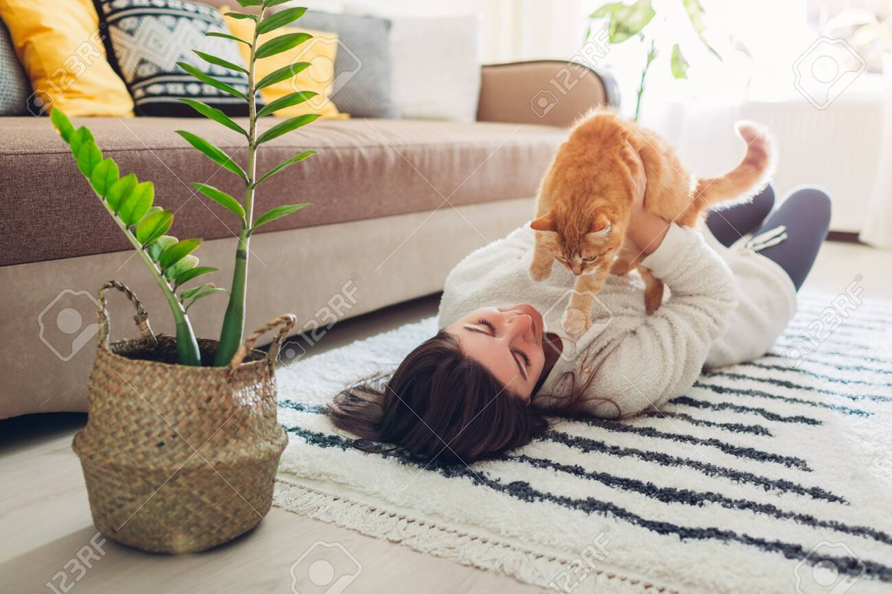 Young woman playing with cat on carpet at home. Master lying on floor with her pet and holding kitten - 123583512