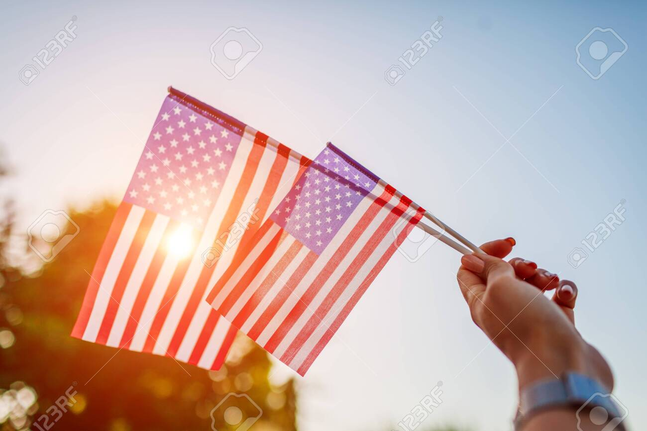 Woman holding USA flag against the blue sky. Celebrating Independence Day of America - 125426995