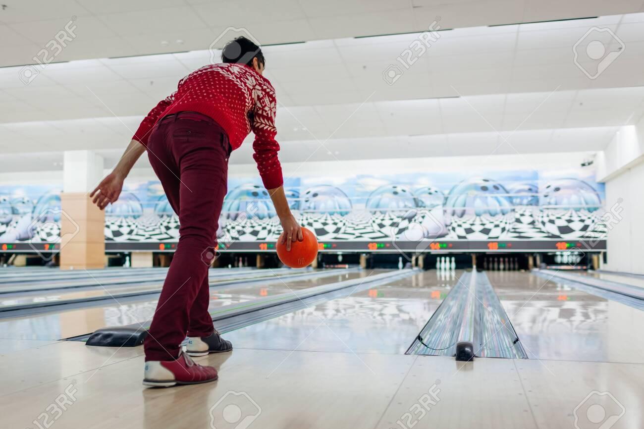 Bowling game. Man having fun playing bowling in club throwing ball on lane. Kegling entertainment. Hobby concept - 141612528