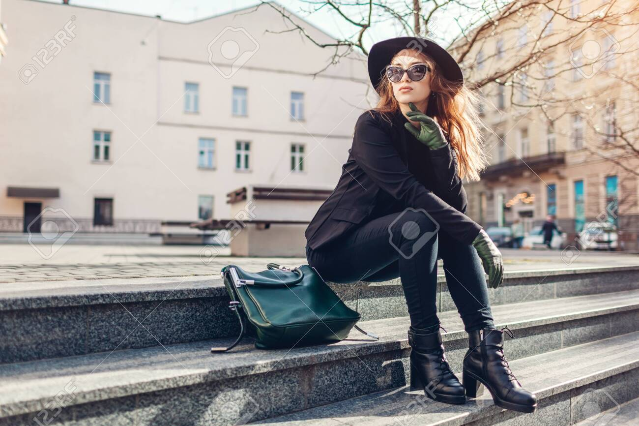 Stylish woman wearing hat, glasses with green handbag and gloves sitting on street outdoors. Spring clothes, accessories. Female fashion. - 141615113