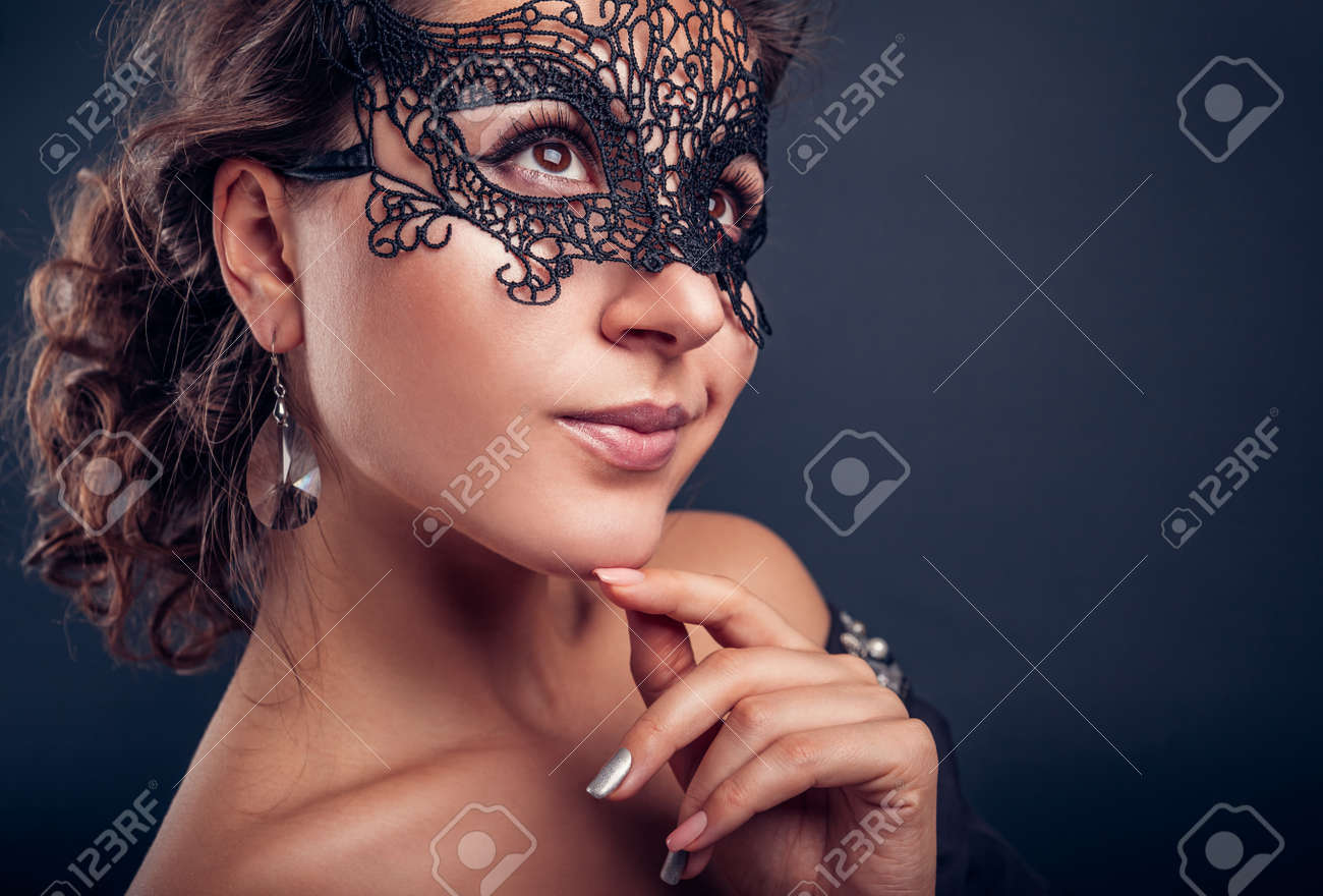 New year masquerade party. Beautiful young woman wearing black lace carnival mask and jewellery. Fashionable look. - 159297546