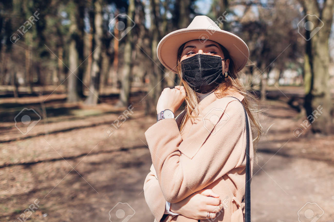 Stylish woman wears reusable mask outdoors during coronavirus covid-19 pandemic in empty spring park. - 168610567