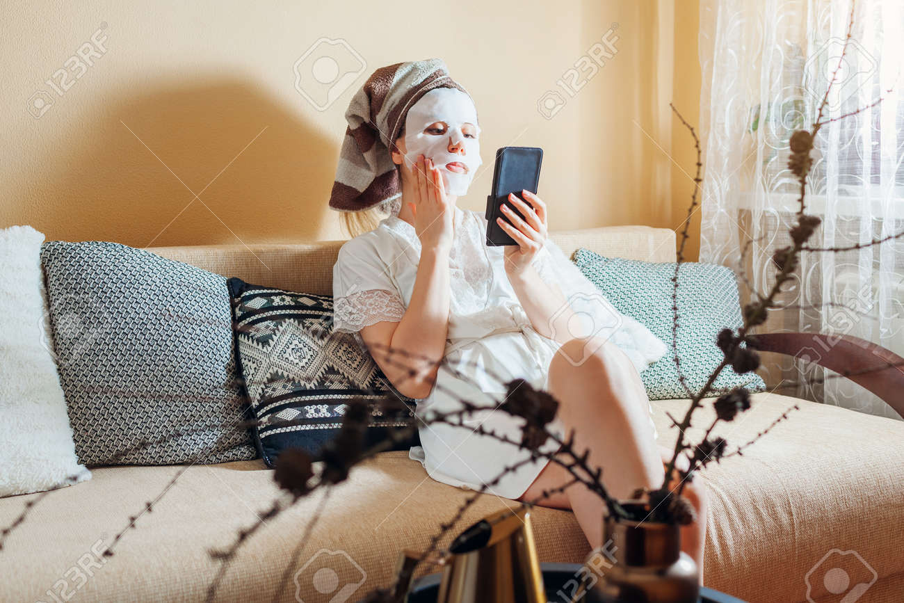 Young woman with facial sheet mask applied looks at smartphone at home after bath relaxing on couch. - 168610572
