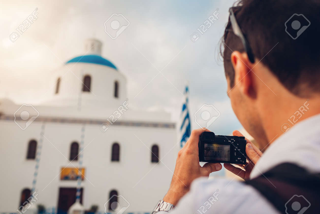 Santorini traveler man taking photo of church with blue dome and flag in Oia, Greece on camera. Tourism, traveling, summer vacation. Traditional architecture - 168610453
