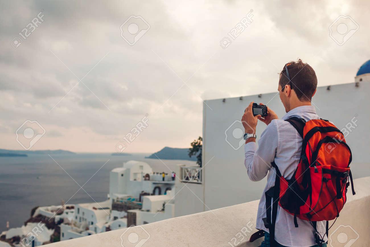 Santorini traveler man taking photo of Caldera from Oia, Greece on camera. Backpacker travels during summer vacation. Tourist admiring Aegean sea landscape. - 168610455