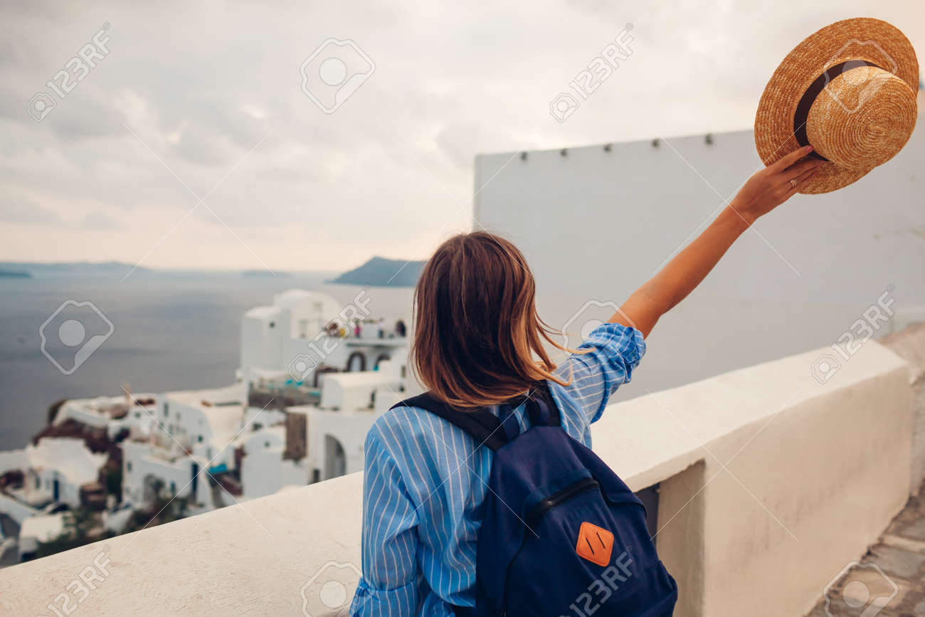 Tourist woman walking on Santorini island, Greece enjoying sea and city architecture landscape. Traveler with backpack admires Caldera view in Oia - 168610456
