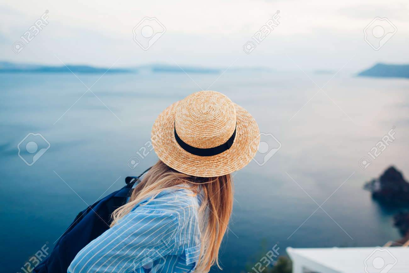 Tourist woman walking on Santorini island, Greece enjoying sea landscape. Traveler with backpack enjoys Caldera view in Oia - 168610458