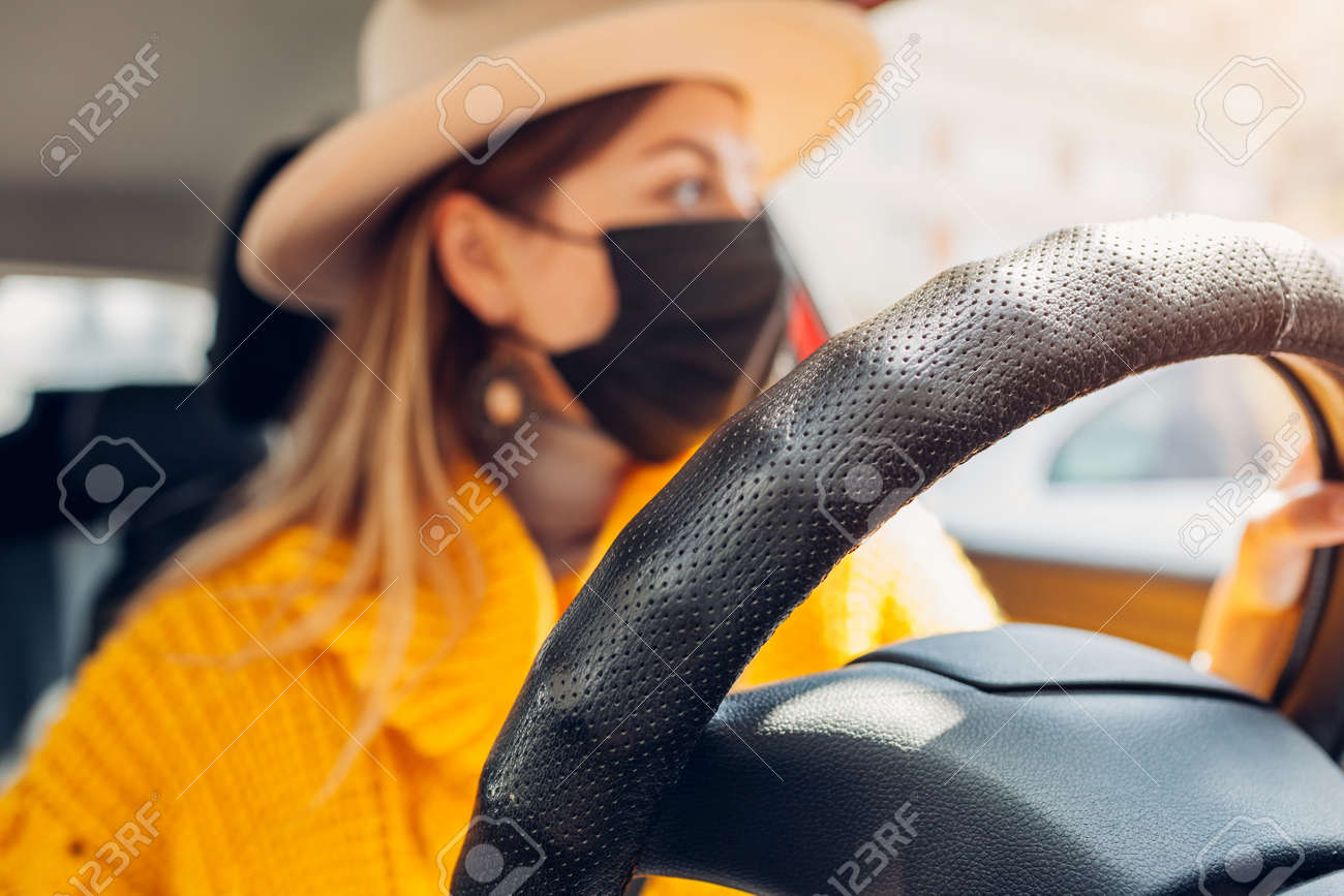 Stylish woman driving car wearing protective mask during coronavirus covid-19 pandemic. Safety measures. Close up of steering wheel - 168610471