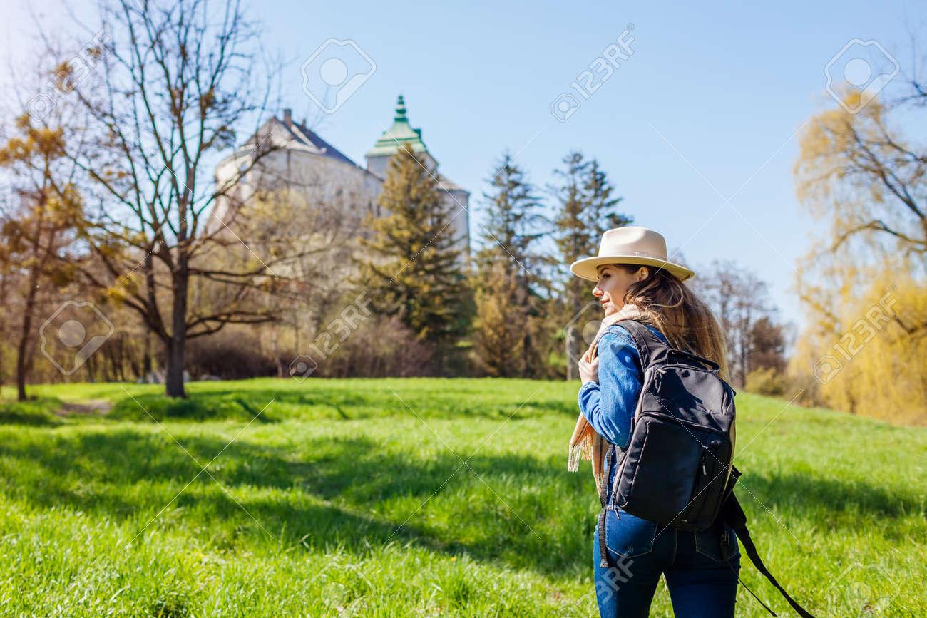 Tourist packpacker walking in Olesko Castle garden. Ancient architecture landmarks in Western Ukraine. Traveling among historic places - 168610430