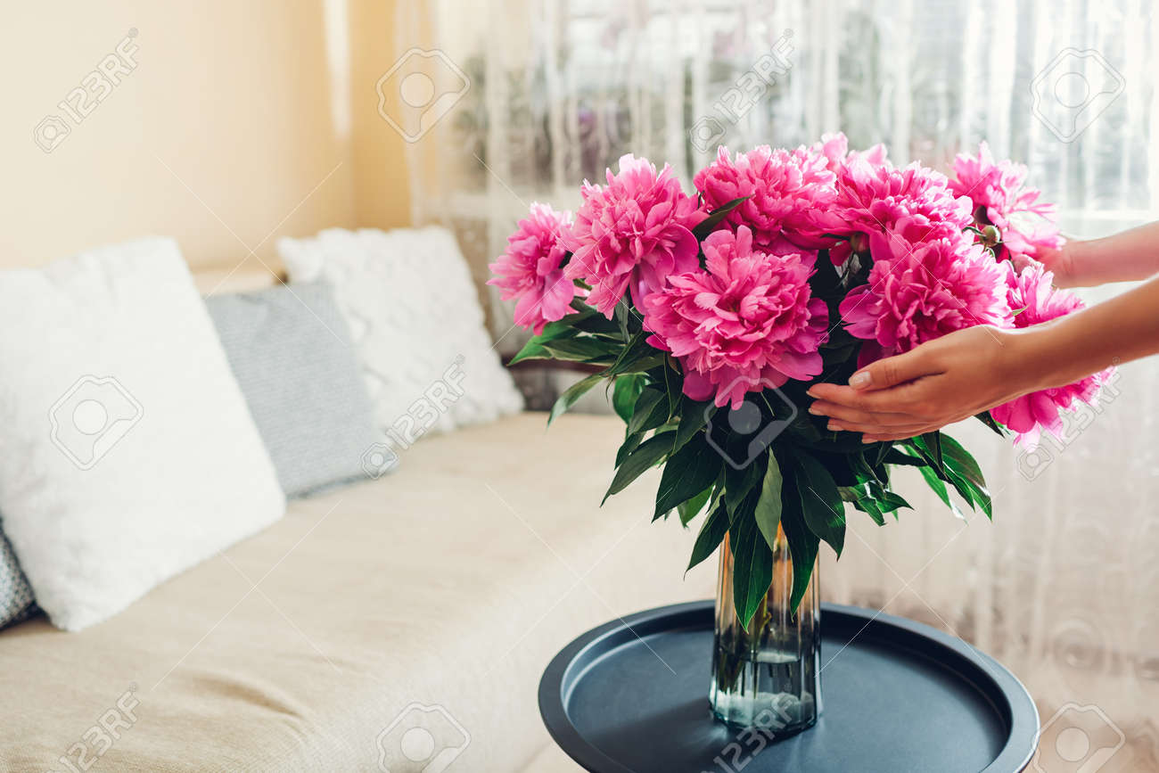 Woman holding bouquet of peonies in vase at home. Pink blooms put on coffee table. Interior and summer decor - 171220834