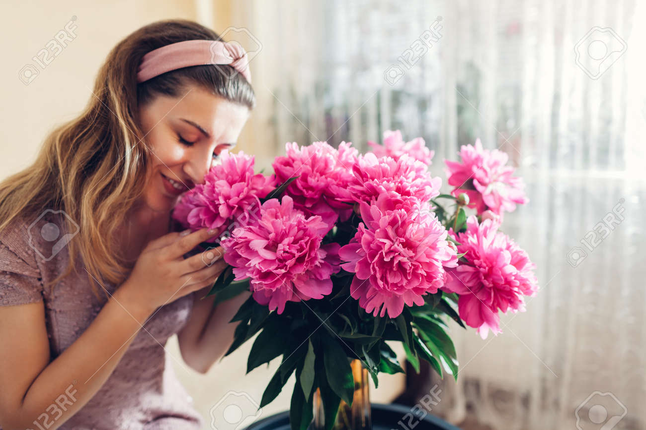 Woman smelling peonies flowers in vase at home. Girl enjoys bouquet of fresh pink blooms. Interior and decor of living room - 171070188