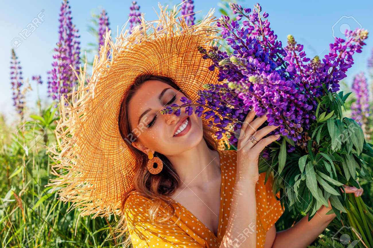 Portrait of young woman holding bouquet of lupin flowers on summer meadow. Stylish girl wearing straw hat - 171431126