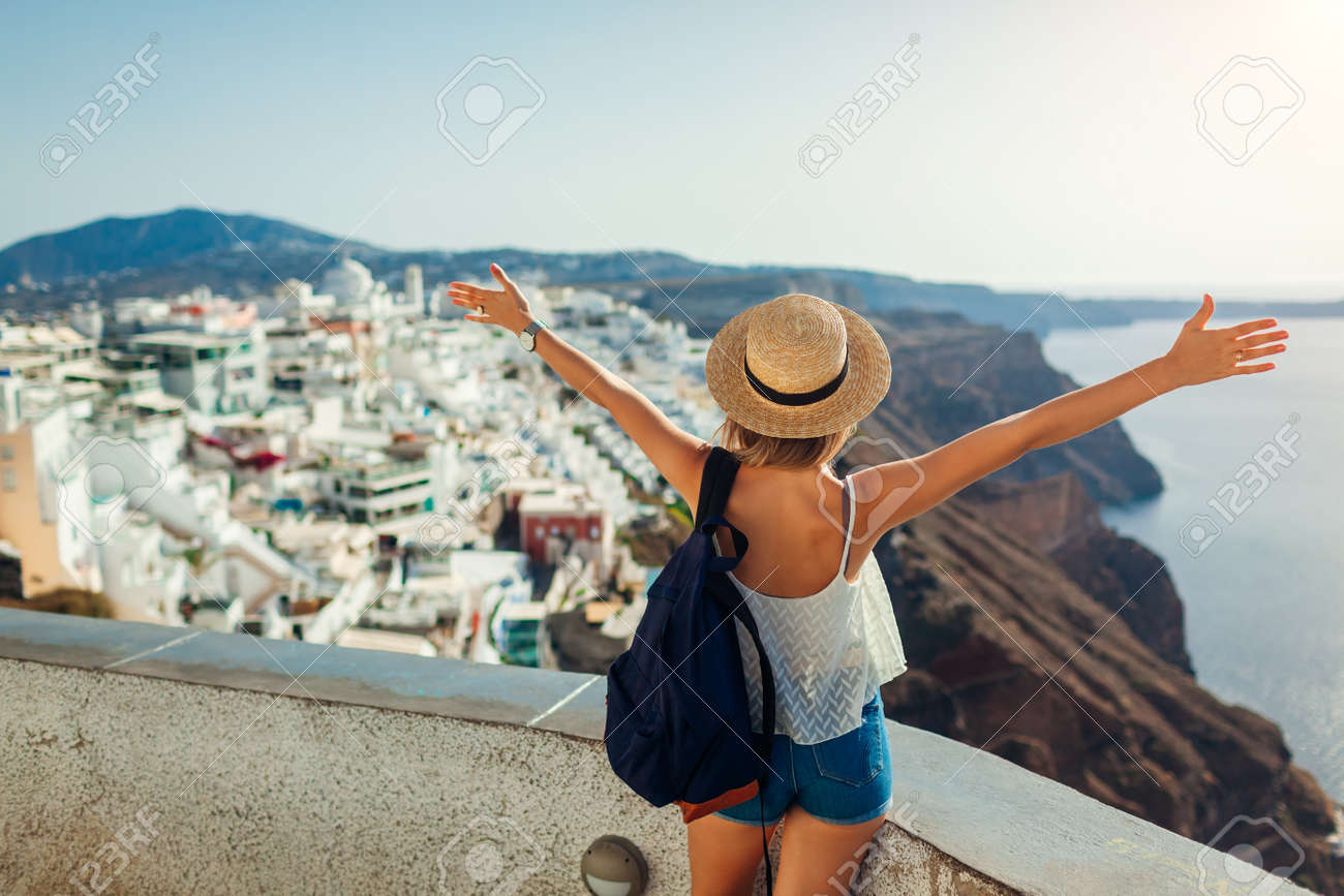 Woman tourist raised arms looking at Caldera sea landscape in Fira, Santorini island. Traveling during summer vacation - 171232594