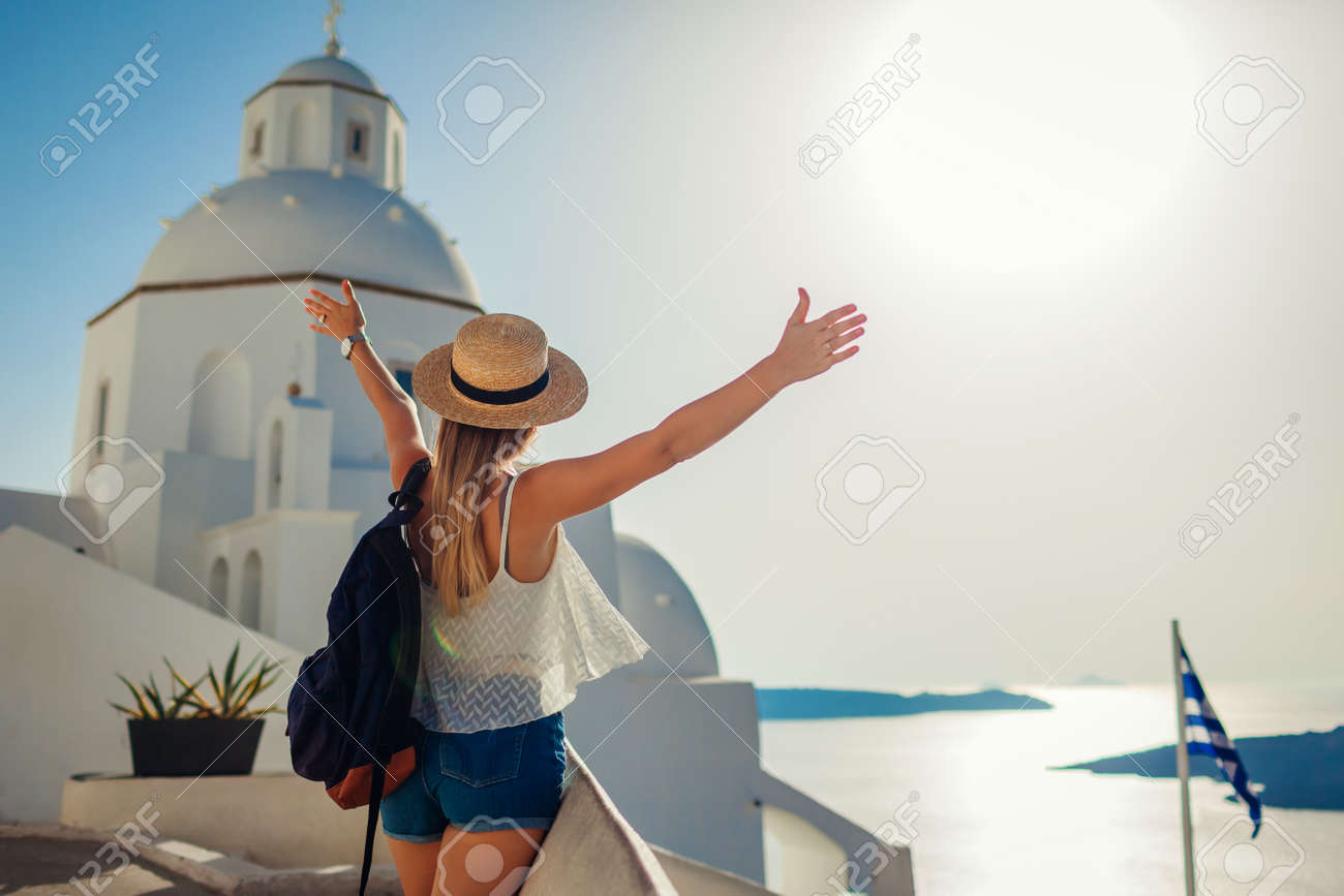 Woman tourist raised arms looking at Caldera sea landscape in Fira, Santorini island walking by traditional church. - 171282234