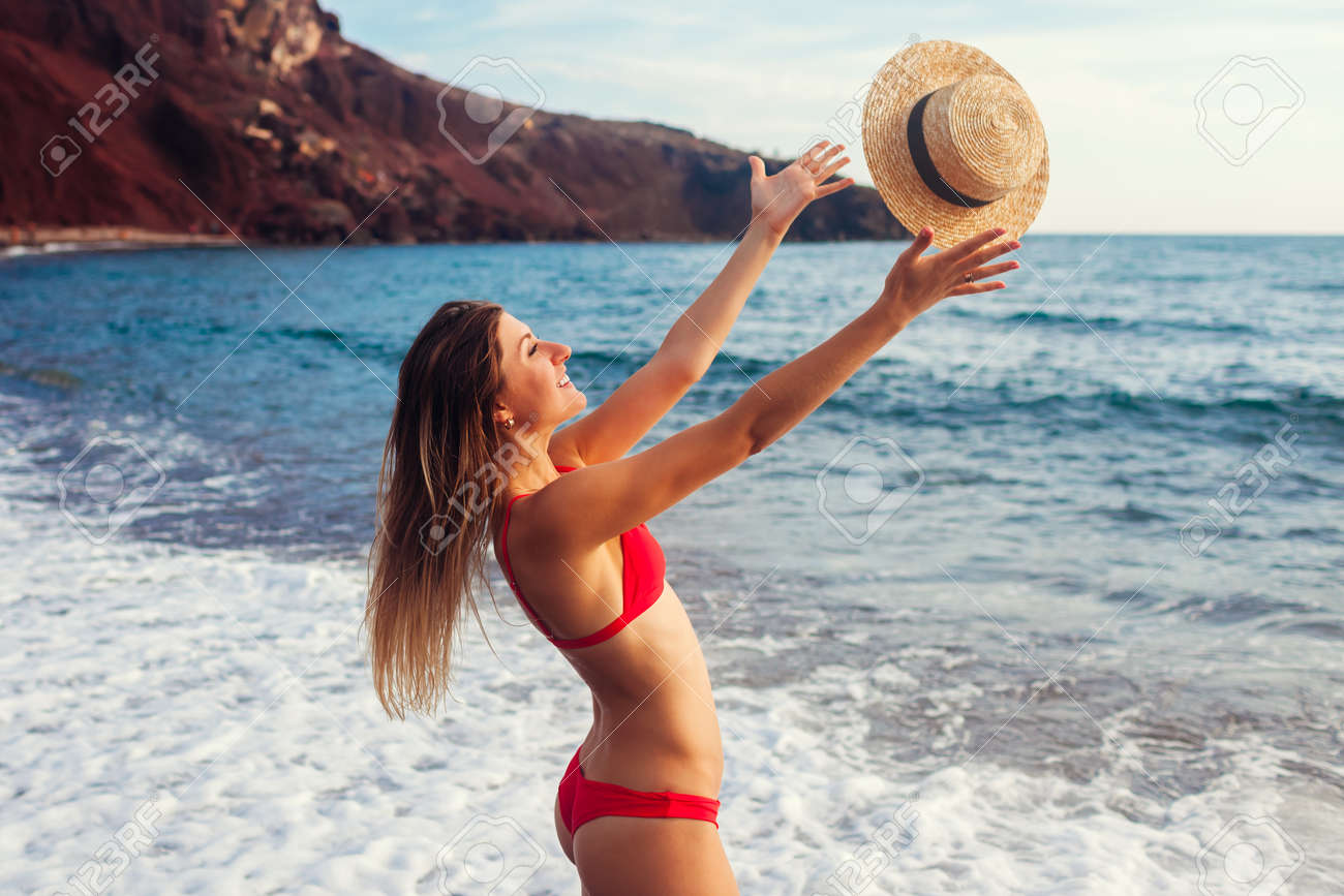 Young woman in bikini plays with hat relaxing on Red beach on Santorini, Greece. Girl enjoys sea and mountain landscape - 171431131