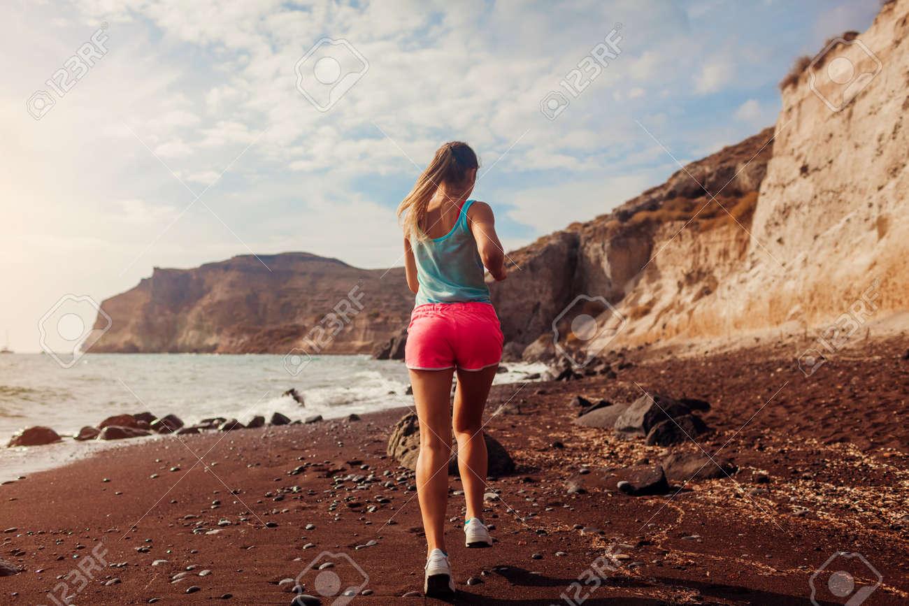 Woman running on Red beach on Santorini island. Female runner jogging during outdoor workout enjoying view - 171334792