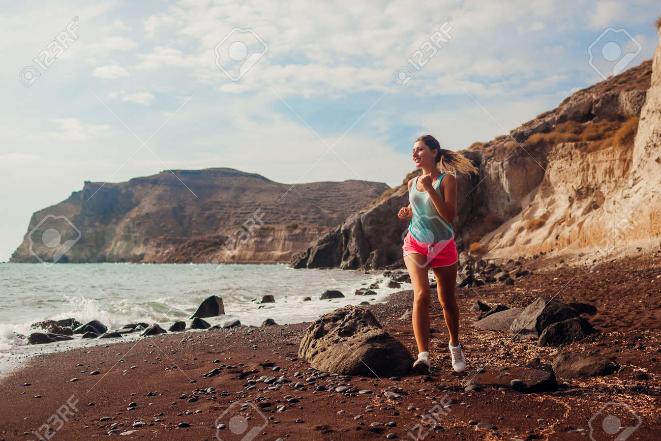 Woman running on Red beach on Santorini island. Female runner jogging during outdoor workout enjoying view - 171391511