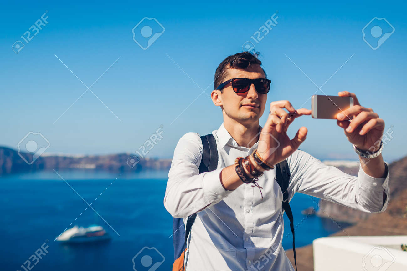 Santorini traveler man taking selfie with Caldera from Fira, Greece on smartphone. Tourist admiring Aegean sea landscape. Tourism, traveling, summer vacation concept. - 171513280
