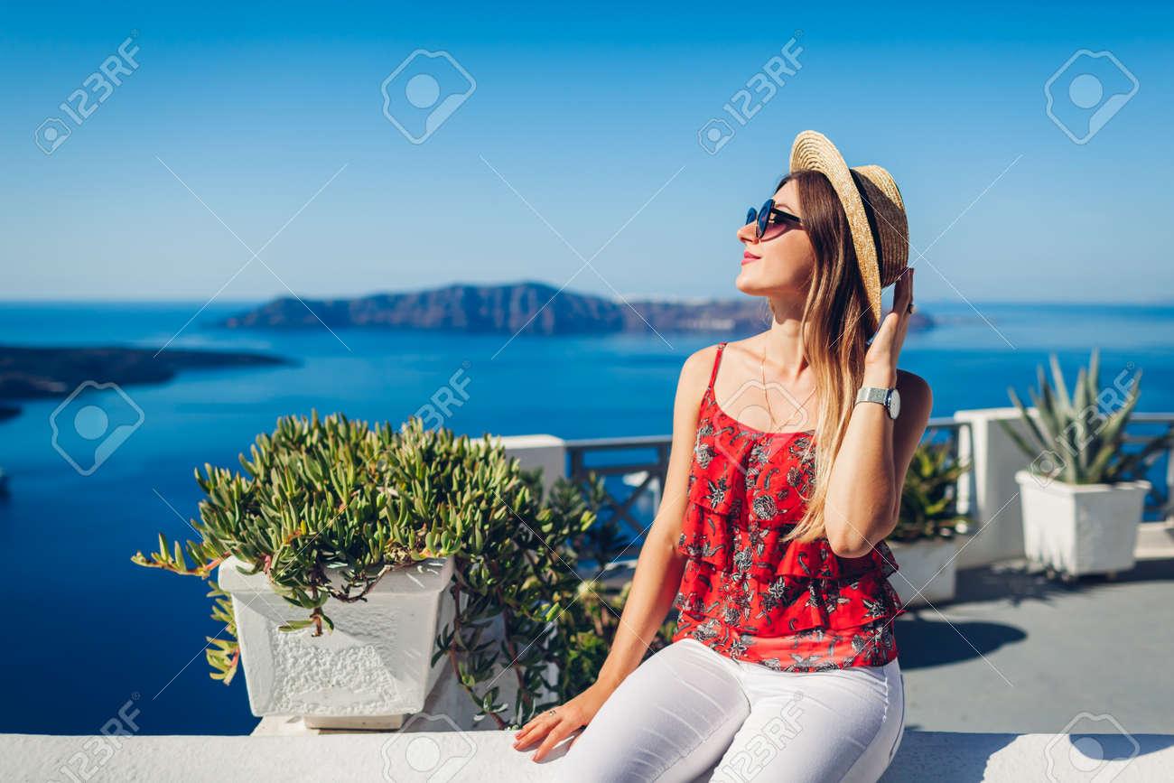 Woman traveler looking at Caldera landscape from Thera, Santorini island, Greece. Tourism, traveling, summer vacation - 171513259