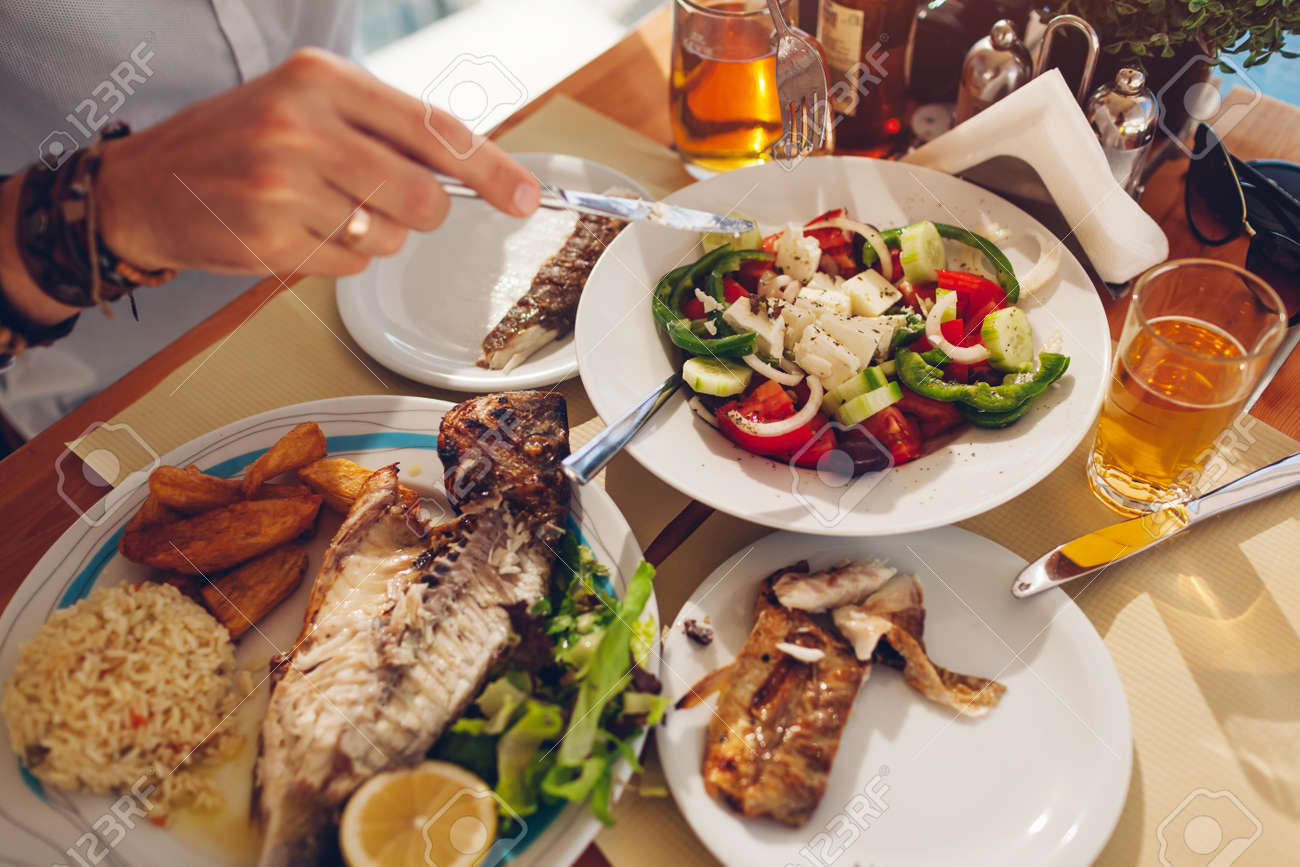Man eats fish with vegetables and greek salad in outdoors restaurant. Fresh seafood dinner served. Close up top view of food - 171513241