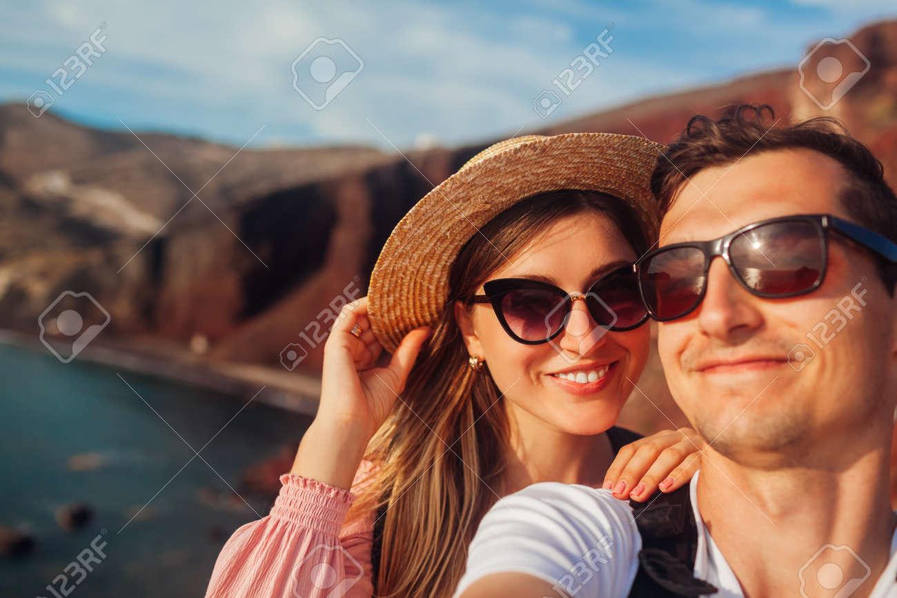 Loving couple takes selfie enjoying honeymoon on Red beach on Santorini island, Greece. Summer vacation. Traveling - 171513221