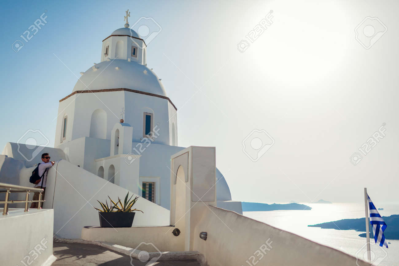 Man tourist enjoying traditional architecture walking by white church on Santorini island with sea landscape in Fira. Greek flag - 171513139