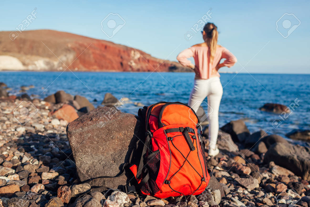 Hiker woman with backpack walking on Red beach on Santorini island, Greece enjoying sea and mountain landscape. Traveling and summer vacation - 171513199
