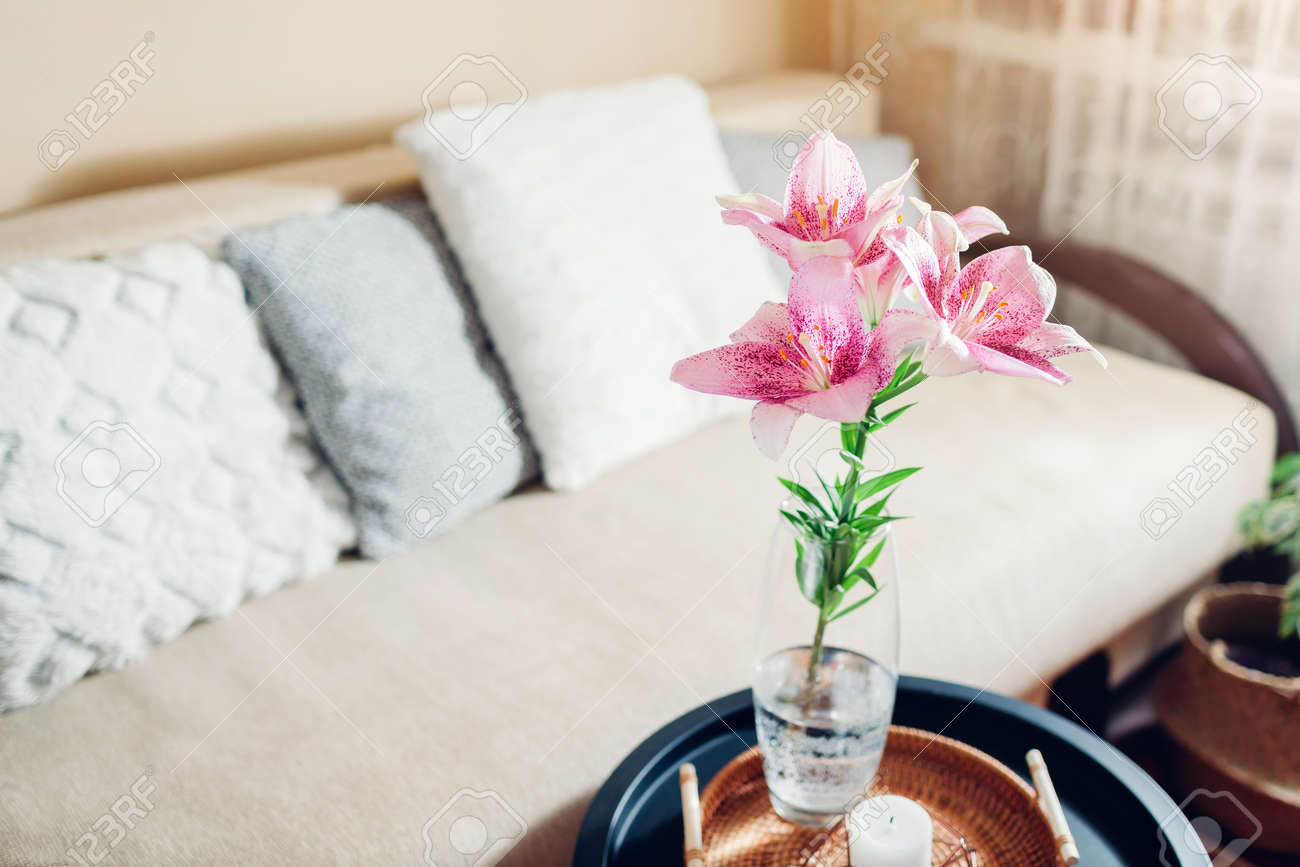 Interior and home decor. Fresh pink lily flowers put in vase in living room by couch. Bouquet of blooms on coffee table - 171922006