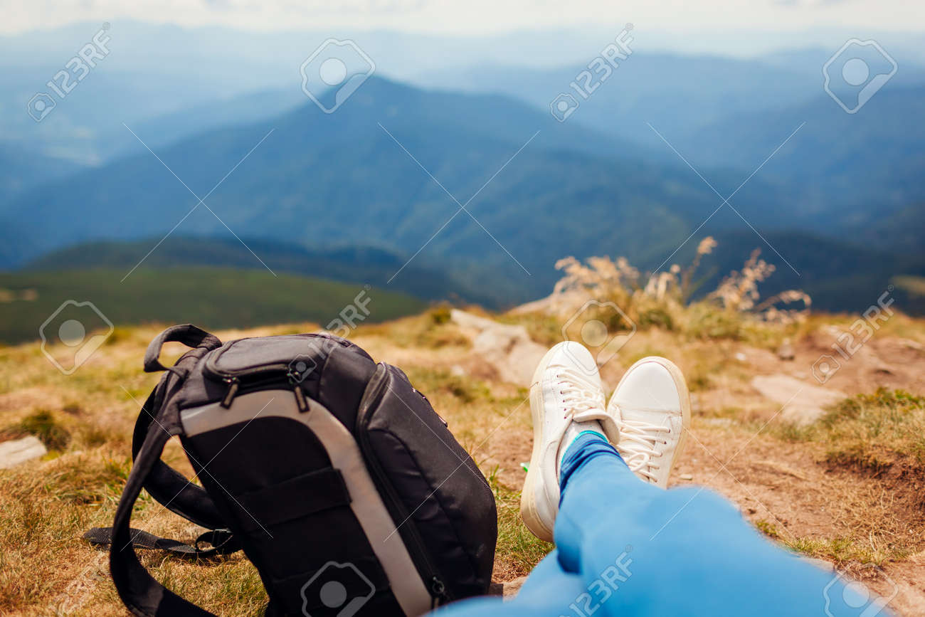 Hiking in Carpathian mountains. Hiker woman relaxing by backpack enjoying landscape. Traveling in summer Ukraine. Close up of shoes - 173065490