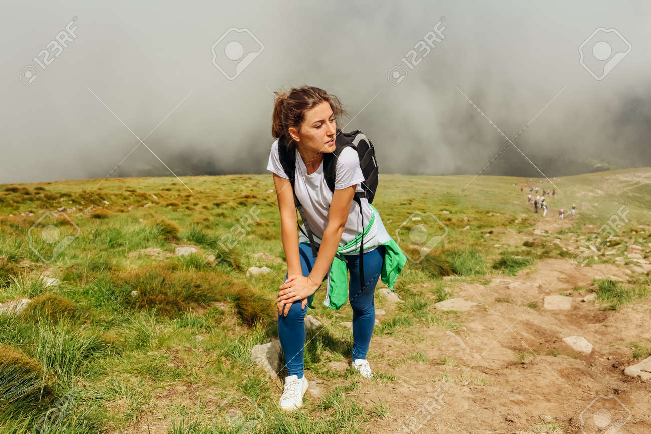 Sportive woman hiker climbing on mountain surrounded with clouds in Carpathians. Tired traveler with backpack resting. Trip to summer Ukraine - 173065508