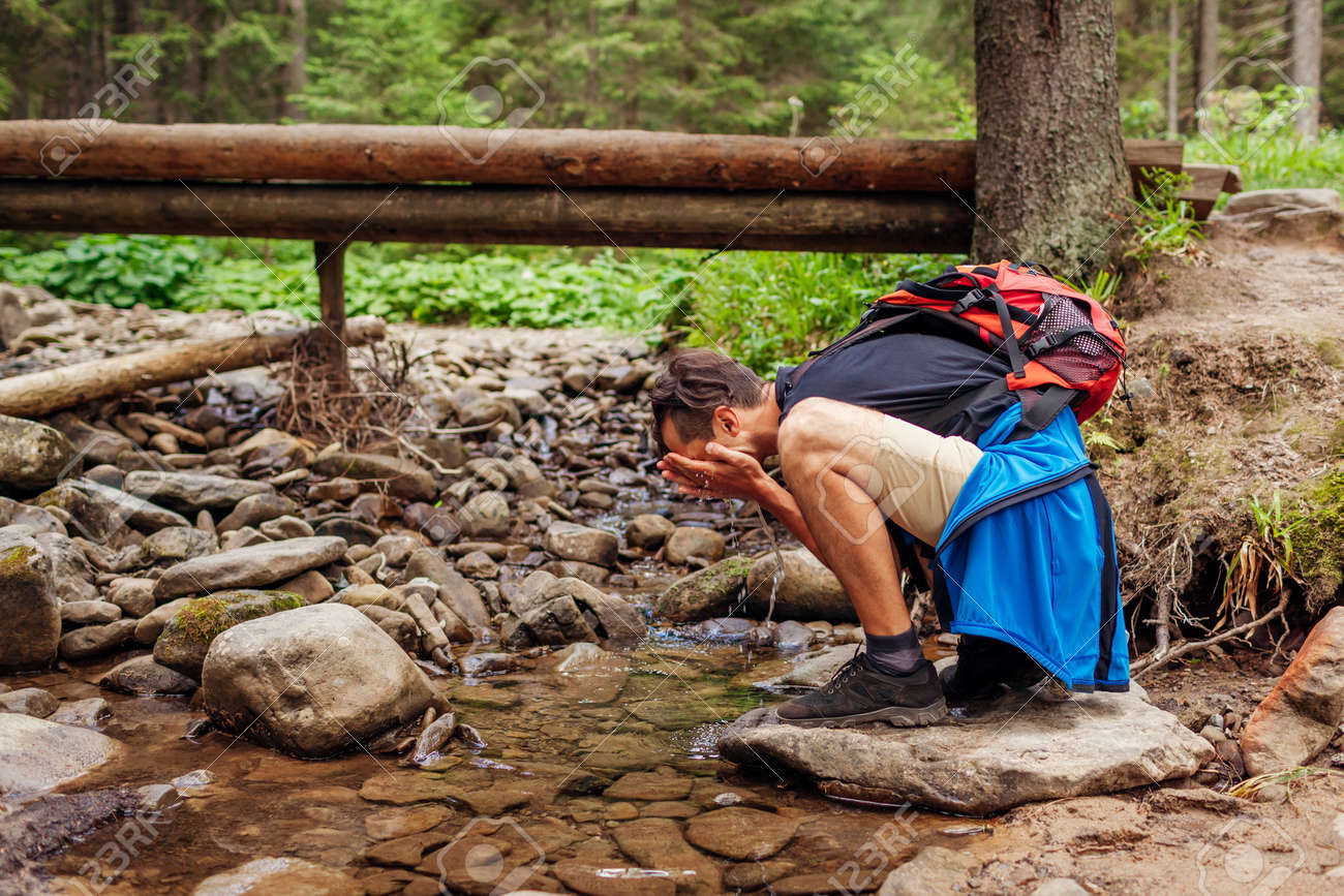 Traveler hiker with backpack washes face in mountain river in Carpathian forest by bridge. Tourist having rest by stream surrounded with summer nature - 173065512