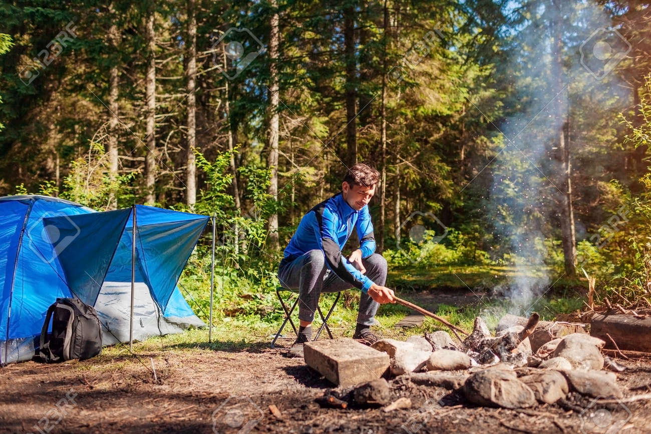Man relaxing by campfire in forest sitting next to tent. Summer camping. Traveling alone enjoying nature - 173065515