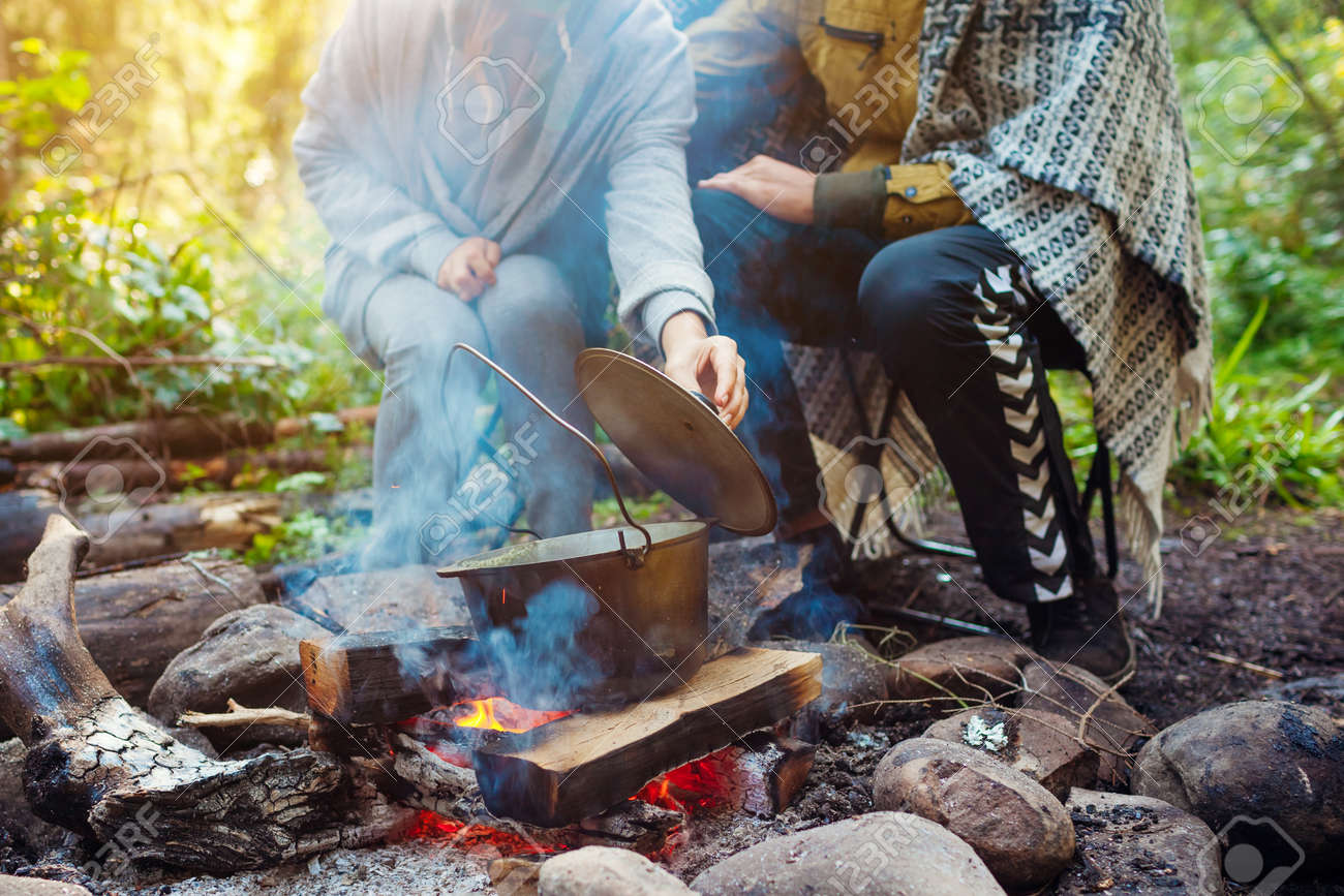 Couple of travelers cooking on campfire in cauldron lifting pot lid checking food. Camping in summer forest. Traveling and tourism - 173097647