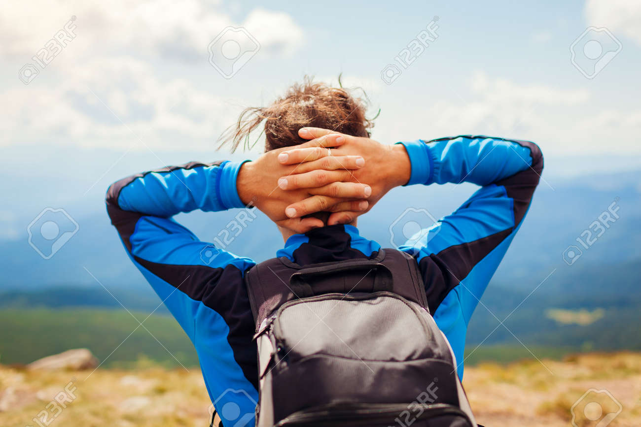 Trip to Carpathian mountains in summer. Happy man hiker with backpack resting on top of Hoverla enjoying landscape. Back view of traveler. Eco tourism - 173130301