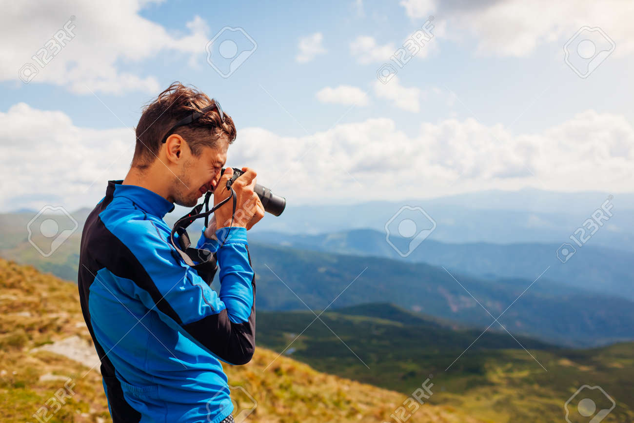 Photographer taking pictures of Carpathian mountains landscape on top of Hoverla. Man hiker using camera to make photos and footage. Traveling wtih digital devices - 173130727