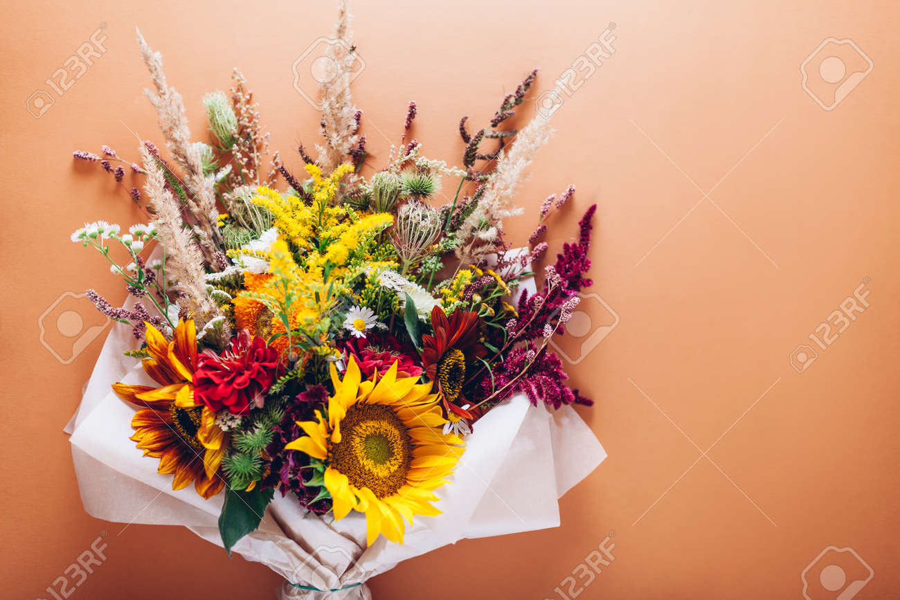Fall bouquet of yellow red orange flowers wrapped in paper and arranged on brown background. Sunflowers, amaranth, daisies with zinnias and grasses - 173239218
