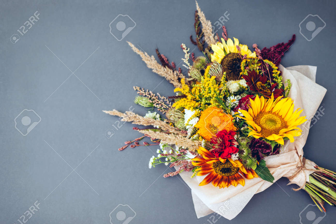 Fall bouquet of yellow red orange flowers wrapped in paper and arranged on grey background. Sunflowers, amaranth, daisies with zinnias and grasses - 173235885