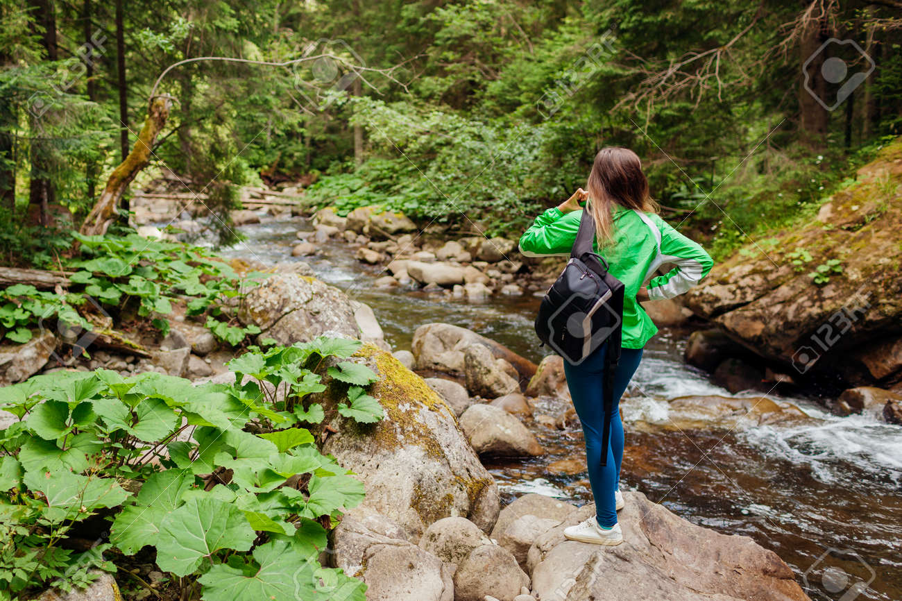 Traveler hiker with backpack enjoys landscape by mountain river in Carpathian forest. Woman tourist enjoys view. Trip to summer Ukraine - 173426604