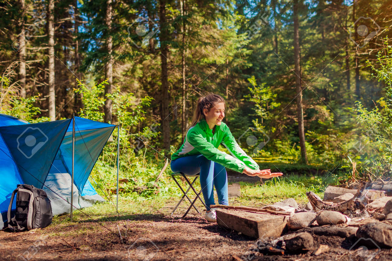 Woman relaxing by campfire in forest sitting next to tent warming hands. Summer camping. Traveling alone enjoying nature - 173430151