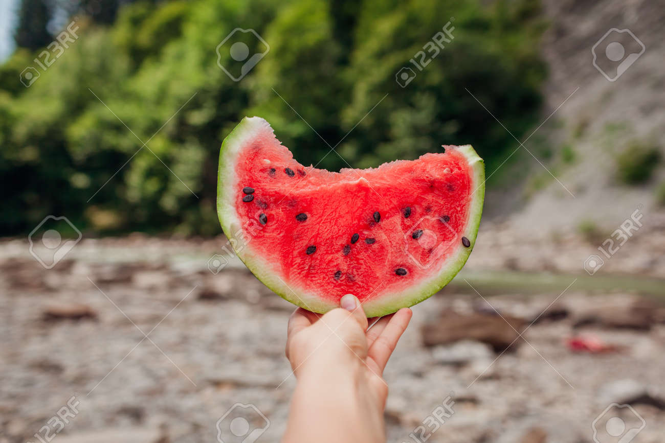 Woman holding piece of watermelon in hand on mountain background outdoors. Snacks eating during traveling in summer. - 173429918