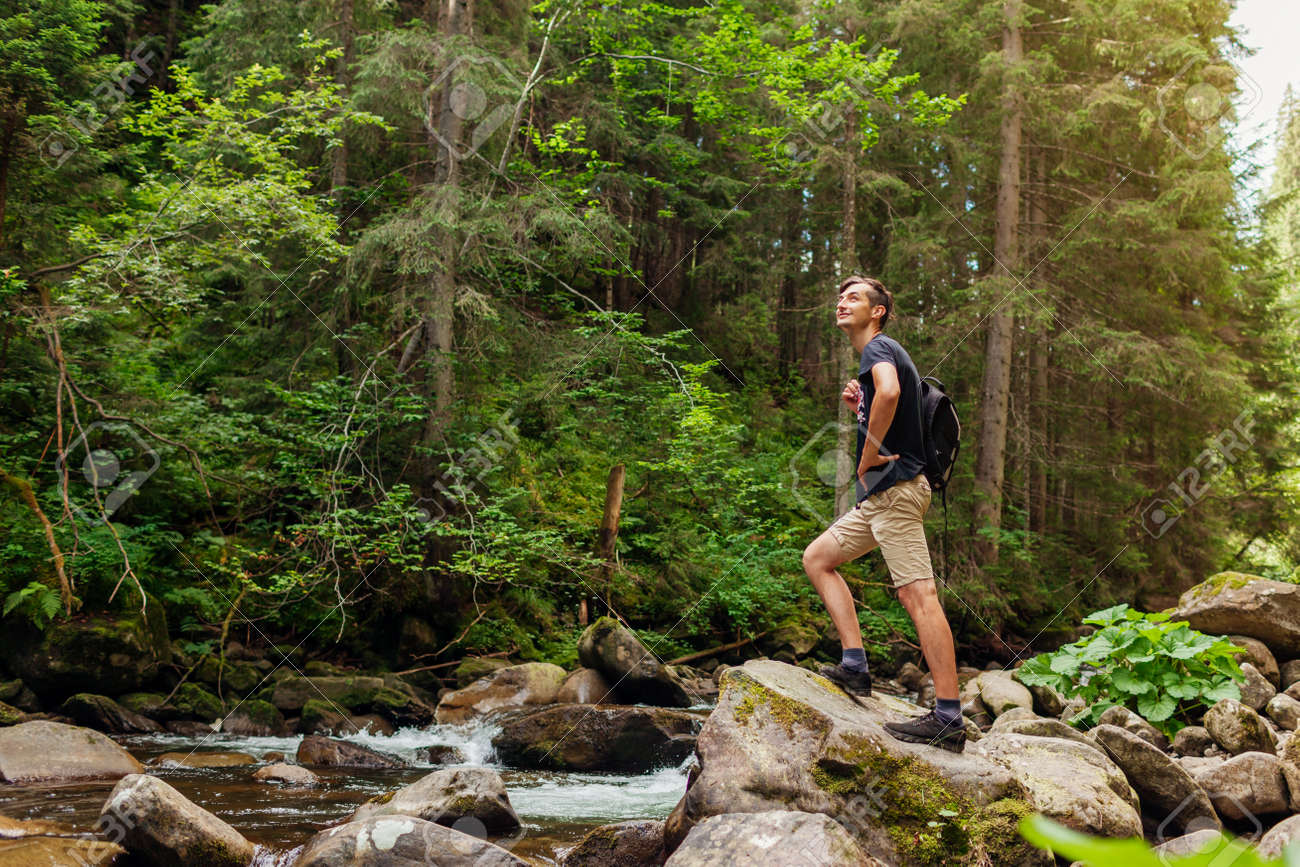 Traveler hiker with backpack enjoys landscape by mountain river in Carpathian forest. Trip to summer Ukraine. Sportive active lifestyle - 173398490