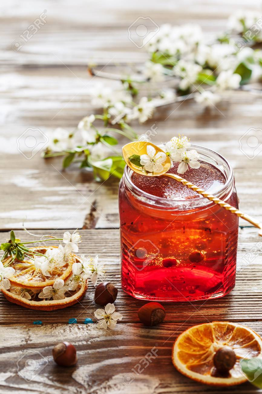 Layered homemade marmalade on the wooden background with cherry flowers, selective focus Stock Photo -